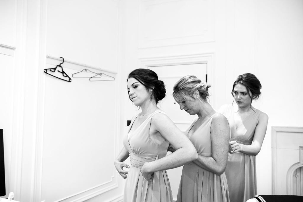 bridesmaids helping each other into dresses