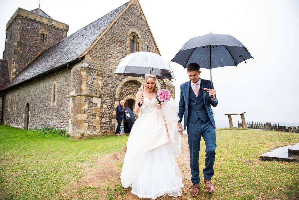 st martha's wedding, couple walk down under umbrellas from the church