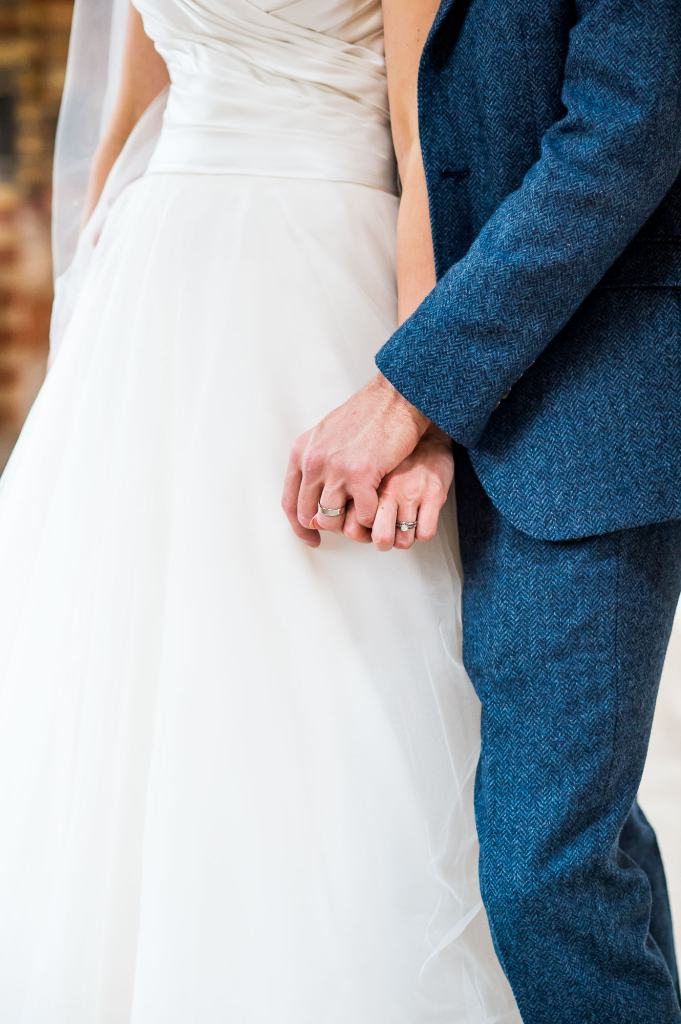 bride and groom hold hands showing off their rings