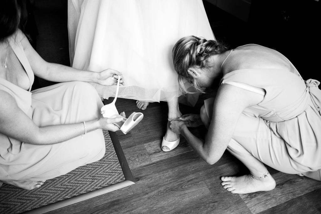 black and white image of bridesmaids helping bride with her shoes