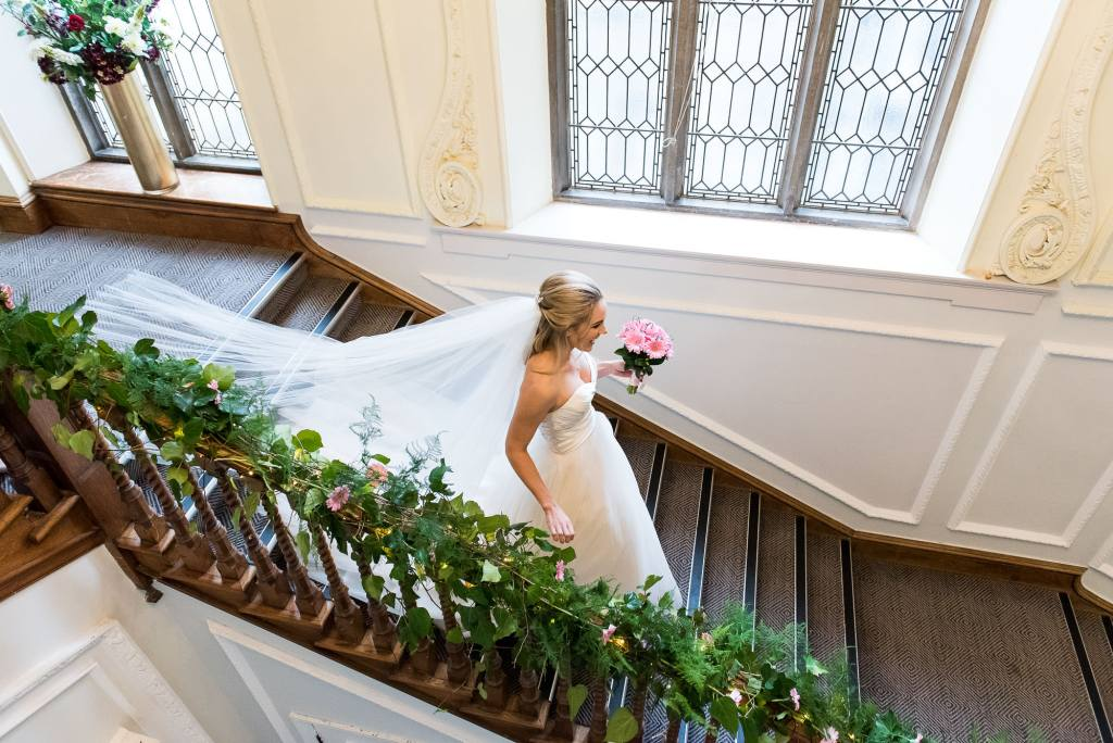 bride descends down the staircase at Horsley Towers