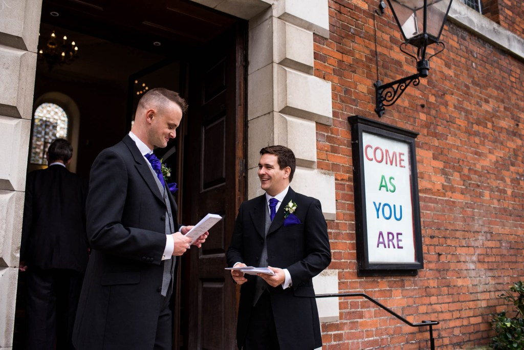 Groomsmen greet guests outside Holy Trinity Church Guildford