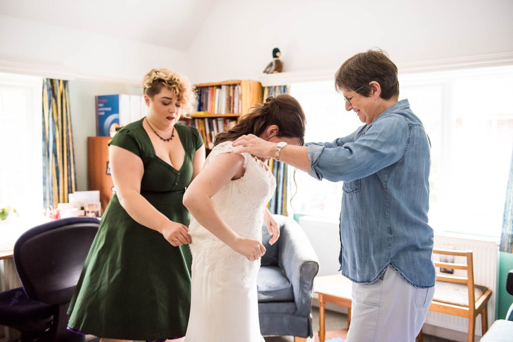 Mother and bridesmaid help bride into her white lace wedding dress