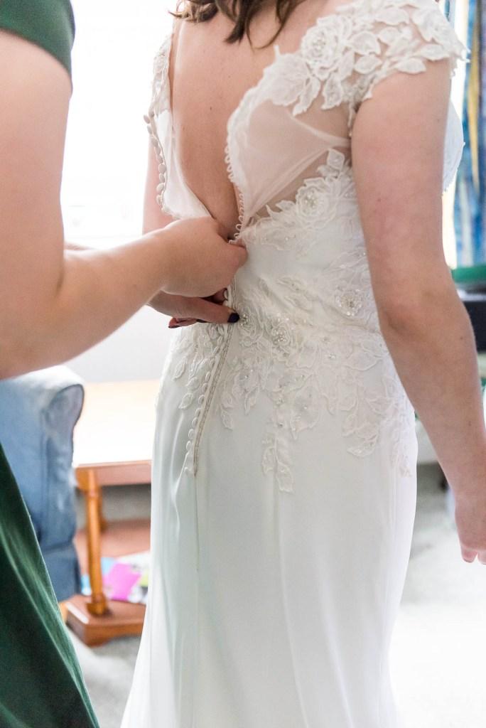 Surrey bride has lace buttons done up