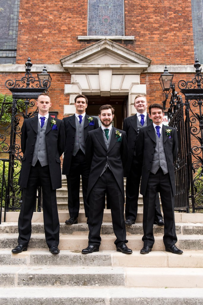 Groomsmen stand on the steps of Holy Trinity Church for formal photographs