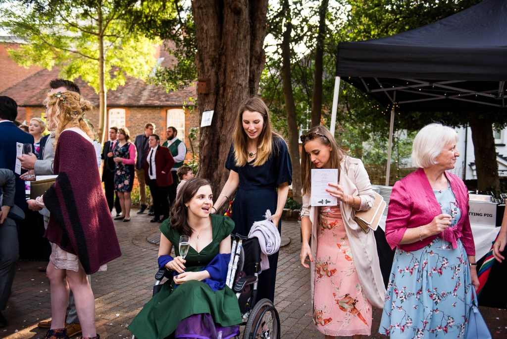 Bridesmaid in a wheel chair is pushed by guests at the reception, Documentary wedding photographer surrey
