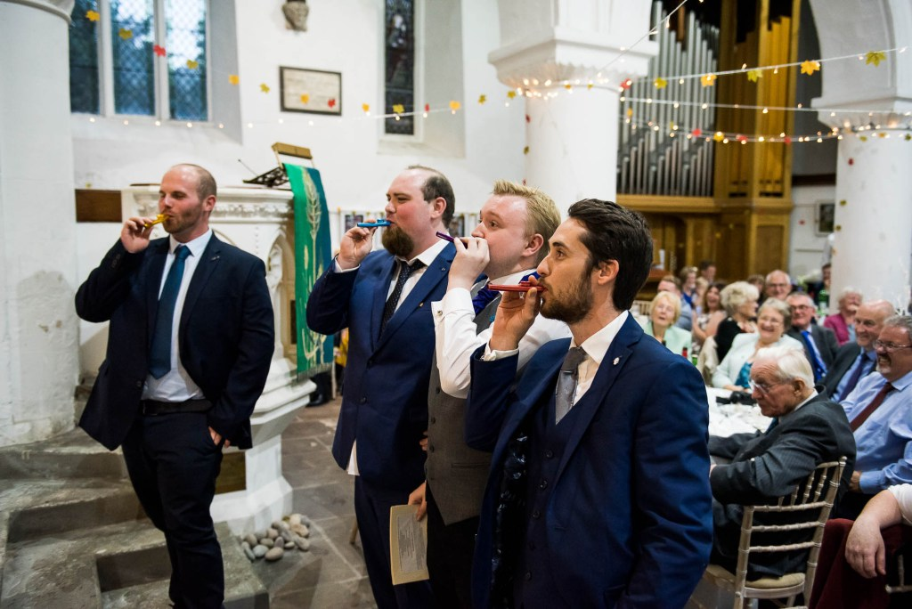 Documentary wedding photographer surrey, Groomsmen sing a song as part of the speeches