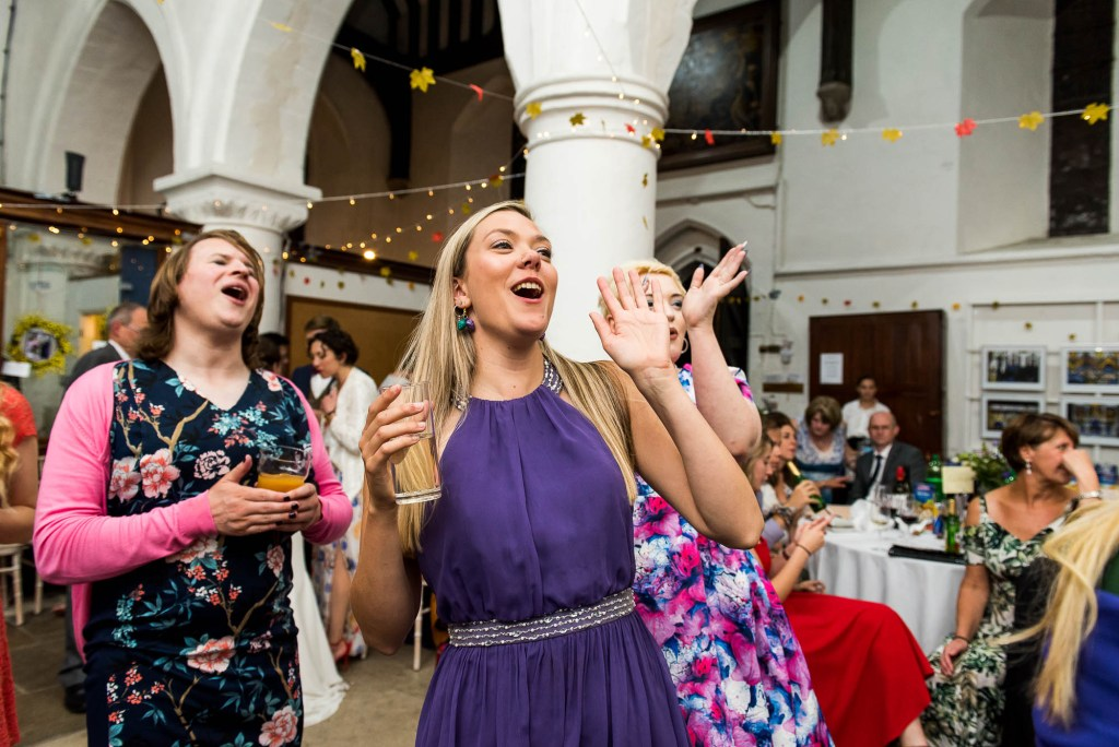 Cheering guests smile and clap at first dance, Documentary wedding photographer surrey