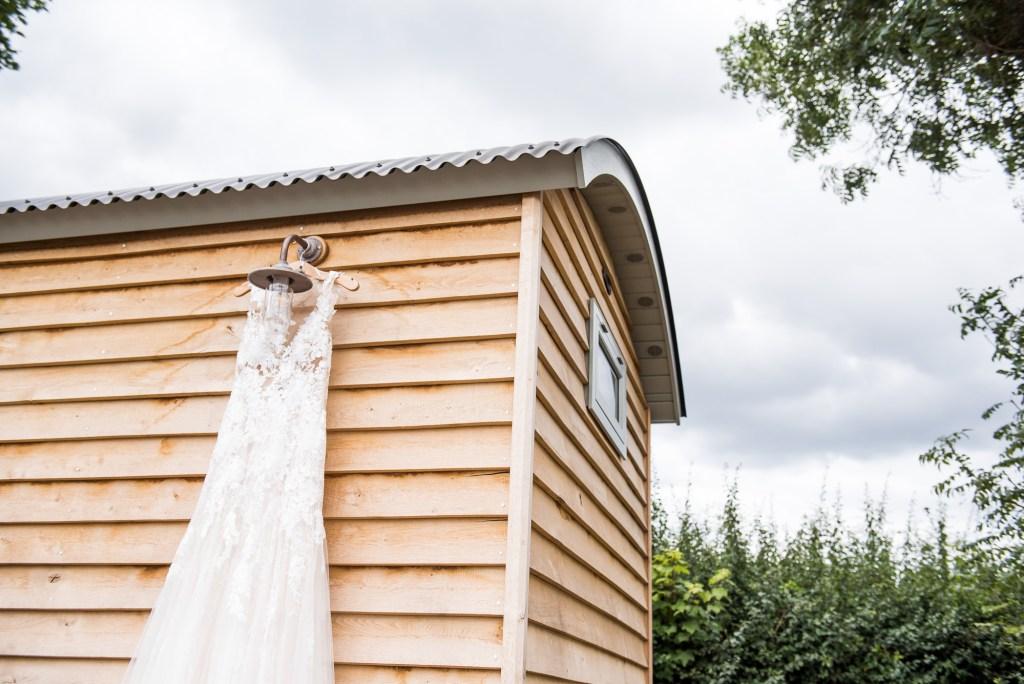 Lace wedding dress hangs on a shepherds hut