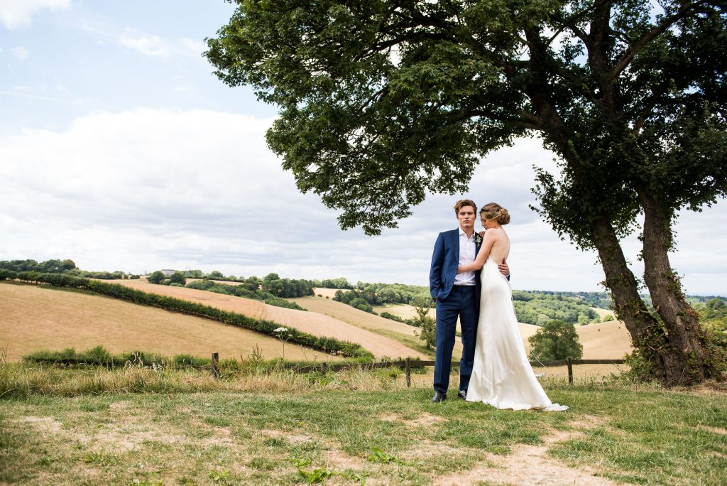 Botley Hill Barn wedding couple stand with the rolling countryside behind them