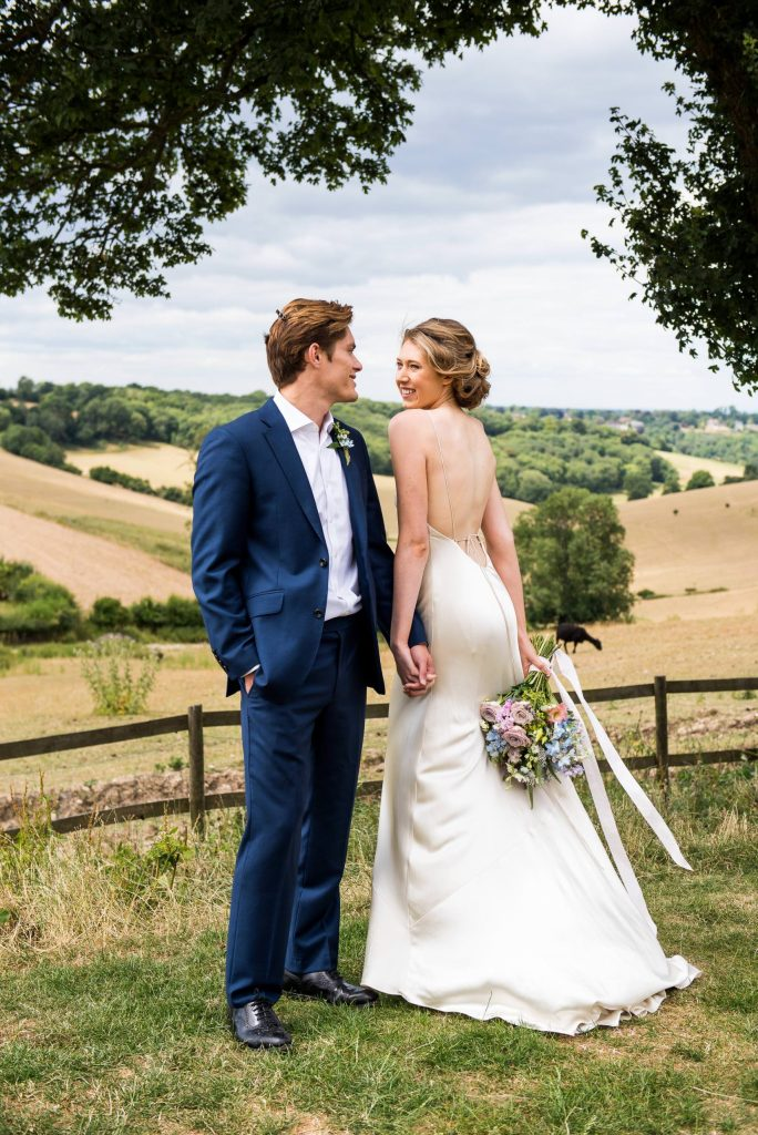 Surrey wedding couple laugh together. Bride wears a backless silk wedding dress and the groom is in a navy blue suit