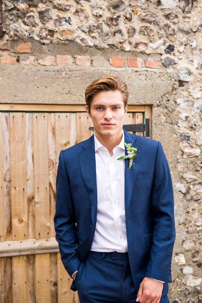 Groom stands in front of rustic barn dressed in a navy blue suit