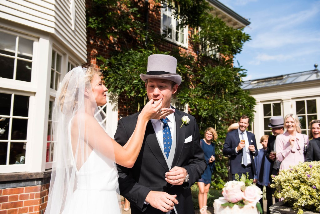 Danish wedding couple feed each other cake at an intimate wedding ceremony in Surrey
