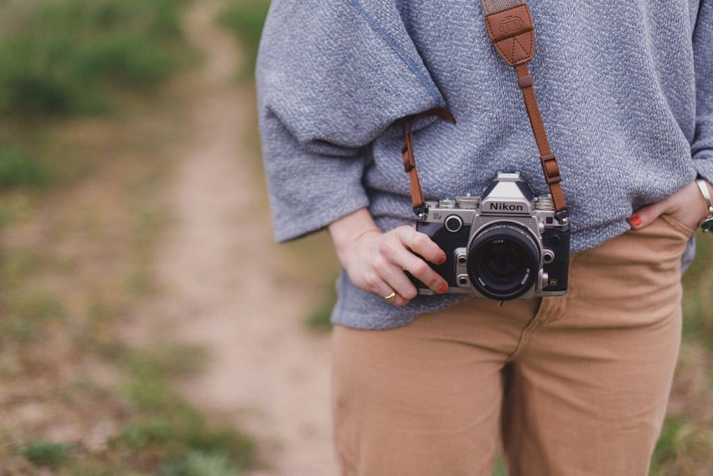 Natural wedding photography // camera hangs by the side of a waist with a hand holding the body