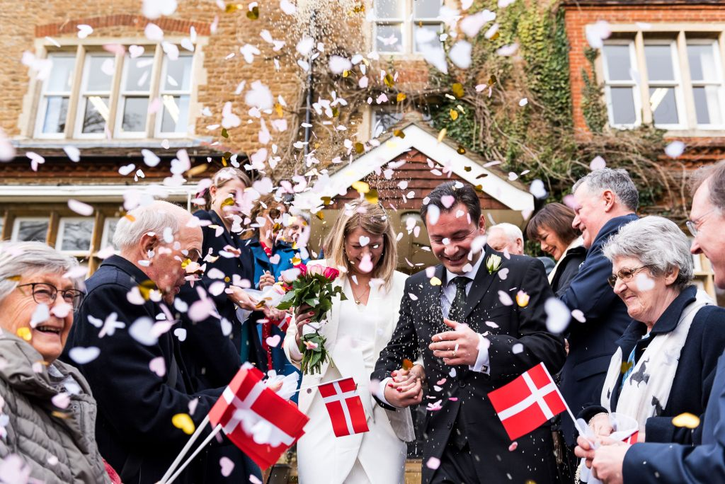 Scandinavian wedding guests wave Danish flags in confetti line