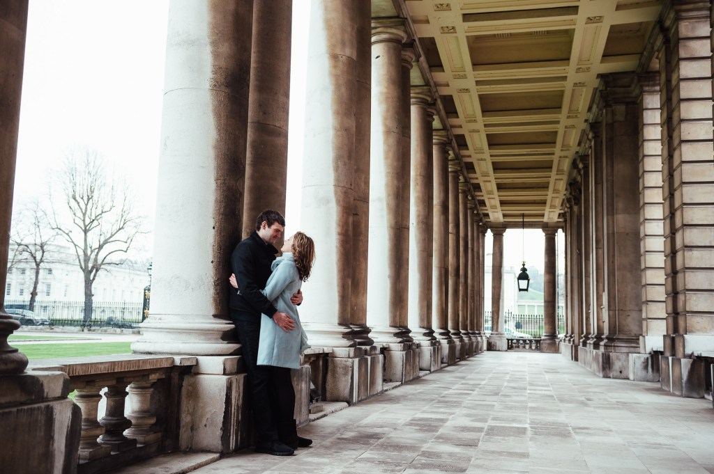 Couple embrace in the columns of Greenwich Maritime College