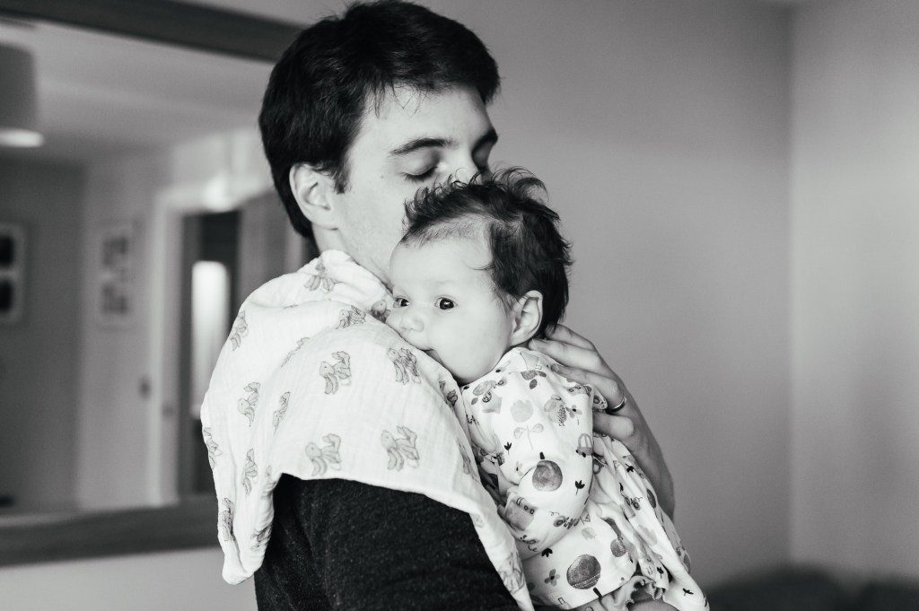 Baby rests on fathers shoulders in Hertfordshire family photography shoot