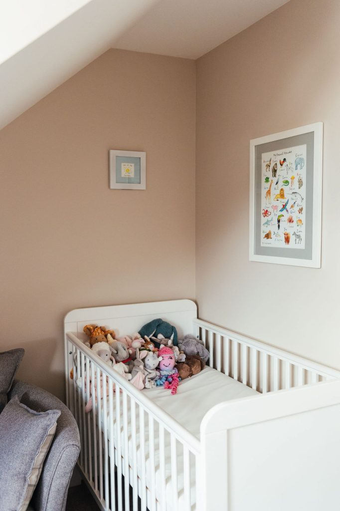 White baby cot filled with stuffed toys