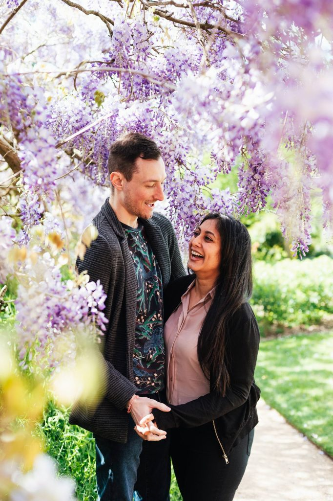 Engaged couple laugh together amongst purple wisteria flowers