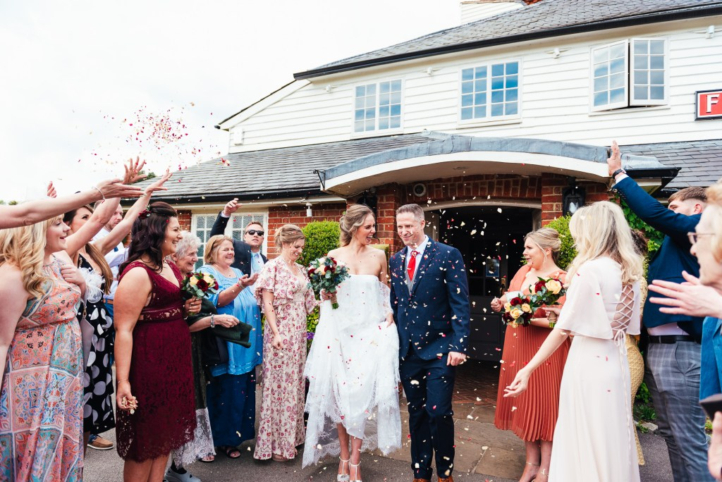 Couple enter the confetti line outside The Elstead Mill
