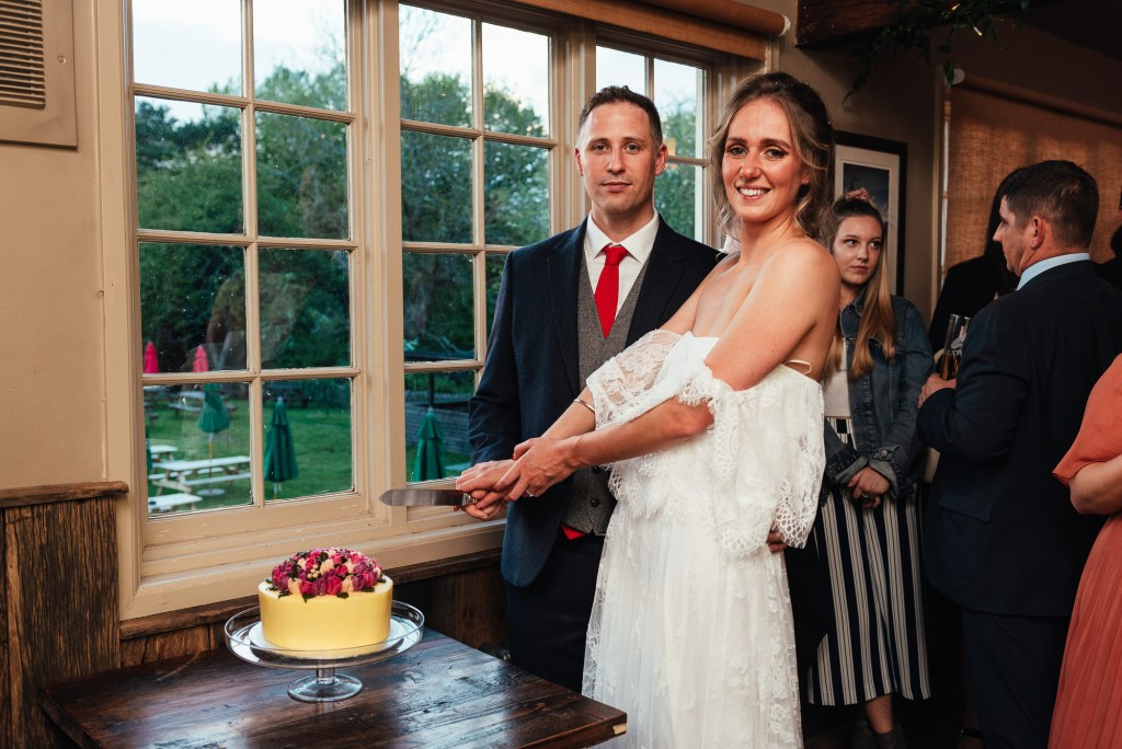 Grace Loves Lace bride with handsome groom cut the cake