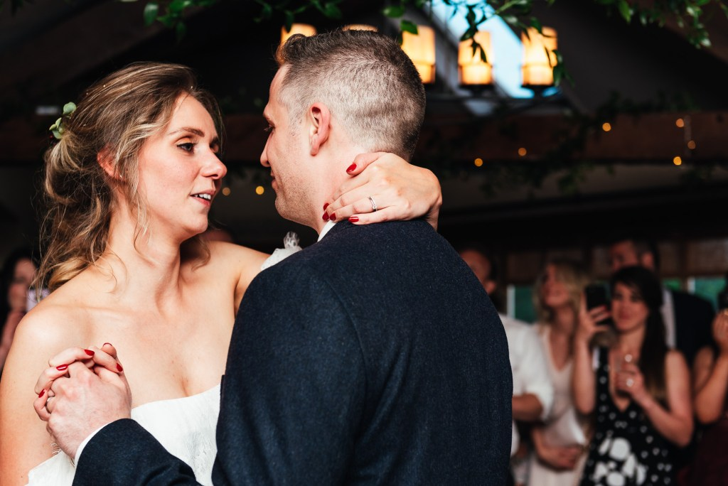Couple share their first dance both looking adoringly into each others eyes