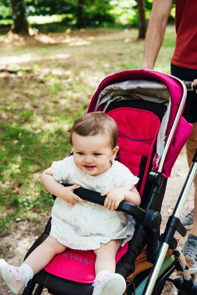 Toddler smiles in her buggy on a walk through Virginia Water