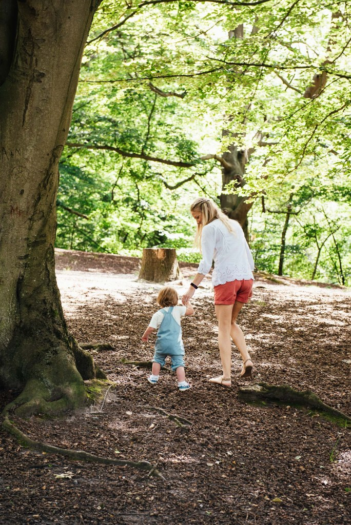Candid mother and daughter moment walking together in the woods