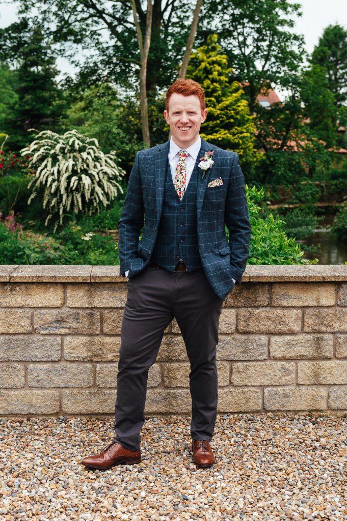 Handsome groom in a tartan suit