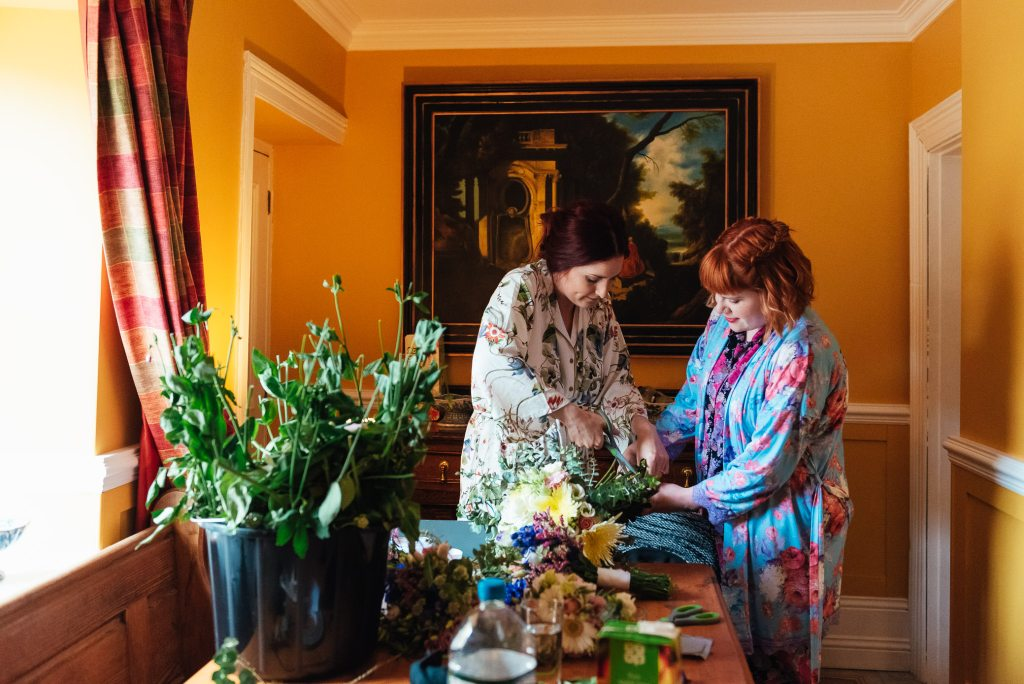 Bride and her maid of honour in matching floral robes making final touches on bouquets