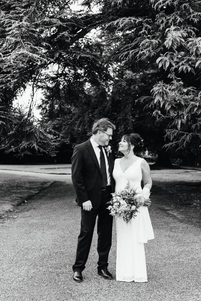 Couple stare lovingly into each others eyes in Oatlands Park Gardens