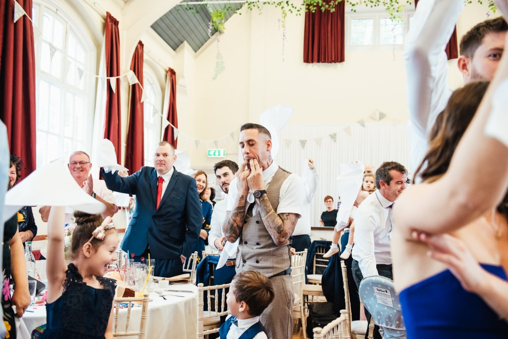 Guests cheer and welcome the bride and groom for DIY village hall wedding