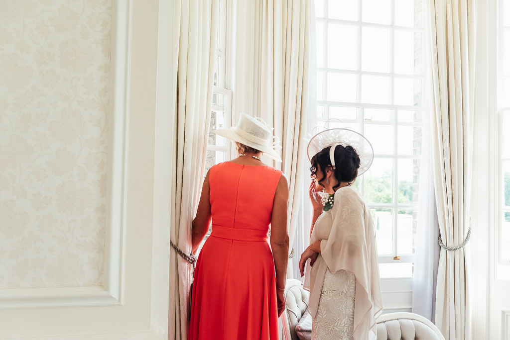 Mothers of the bride and groom watch guests arrive out of the window