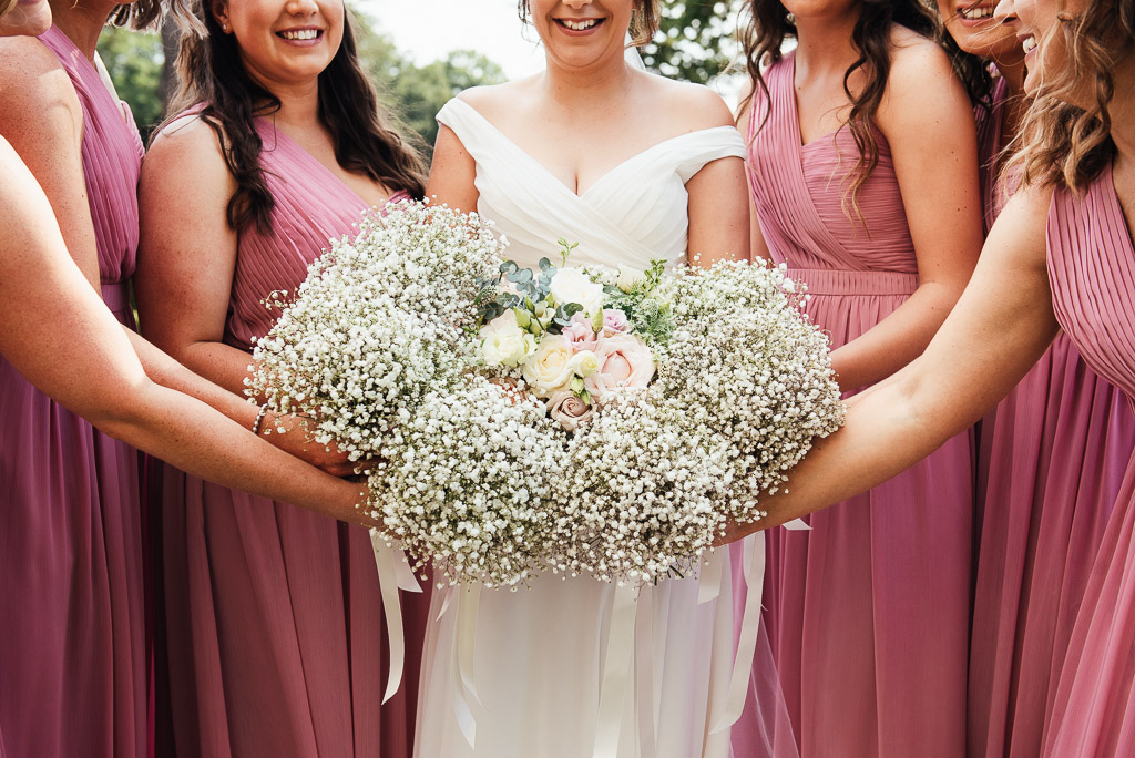 Beautiful bridal party in pastel pink long dresses with matching gypsophila bouquets