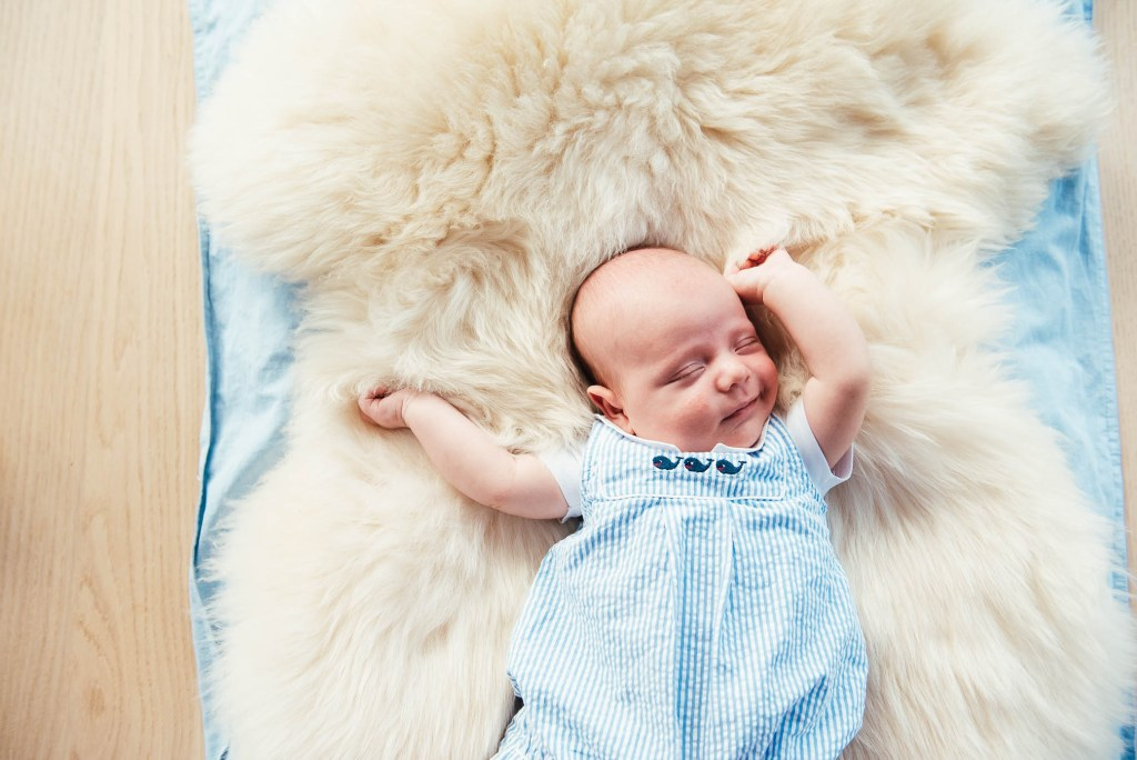 Newborn baby sleeps on a sheepskin rug and stretches