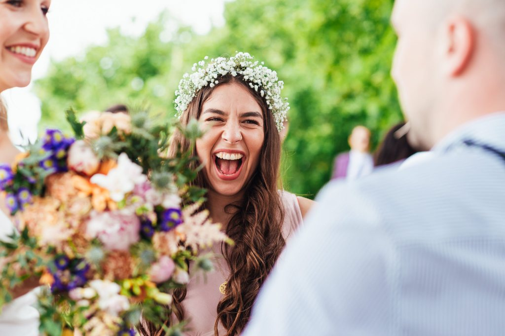 Gorgeous bridesmaid laughs with guest at romantic French outdoor wedding reception