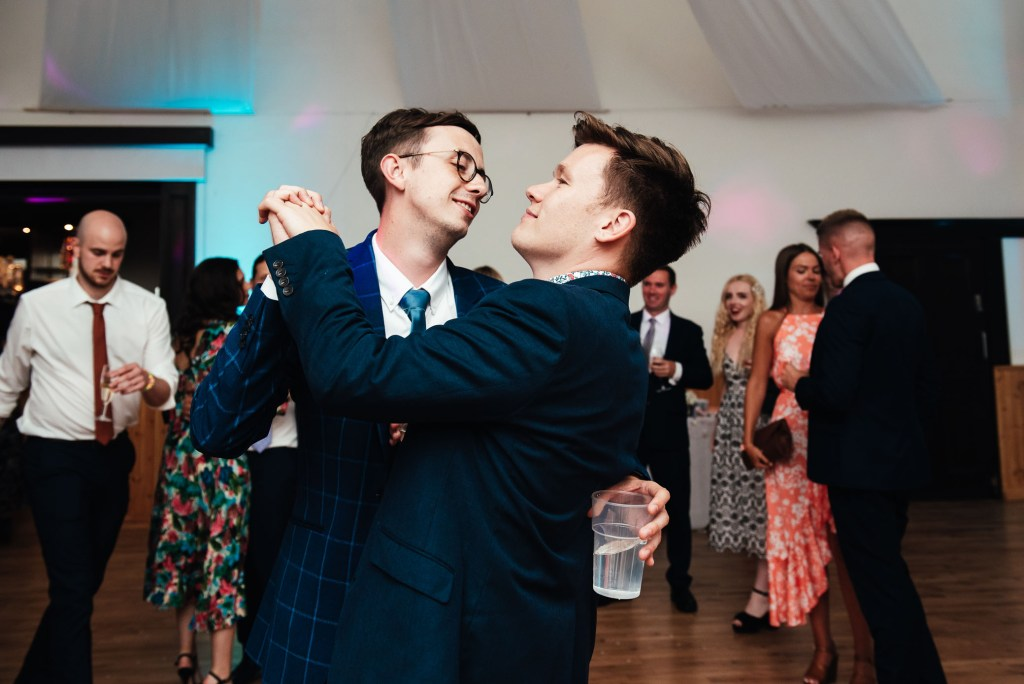 Two men dance together on a wedding dance floor