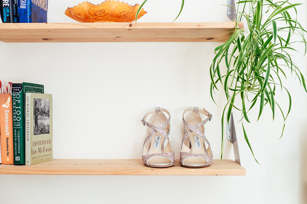 Jimmy Choo wedding shoes sit on a shelf for wedding preparation photography