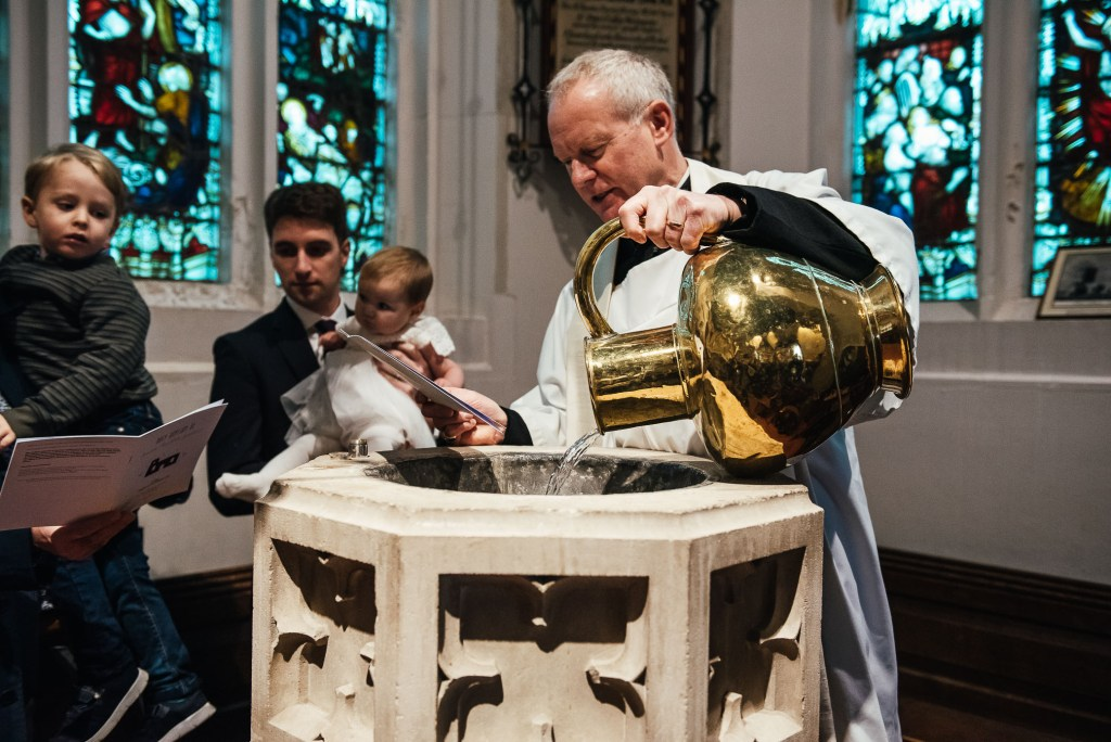 Priest fills basin with holy water
