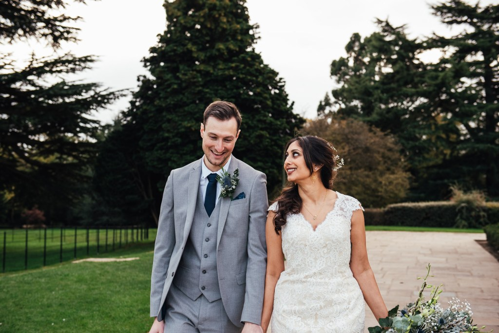 Couple smile together candidly in the grounds of Forty Hall
