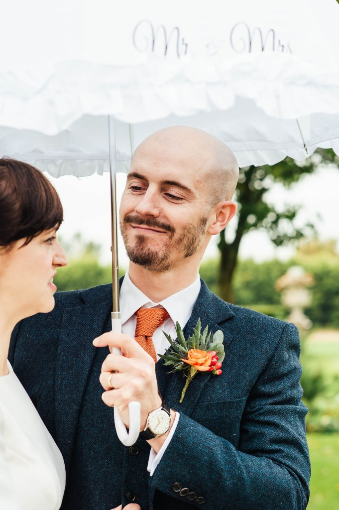 Handsome groom smiles at his bride, Cain Manor wedding photography