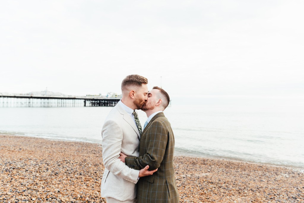 Grooms kiss passionately on Brighton Beach, lgbtq friendly wedding photographer