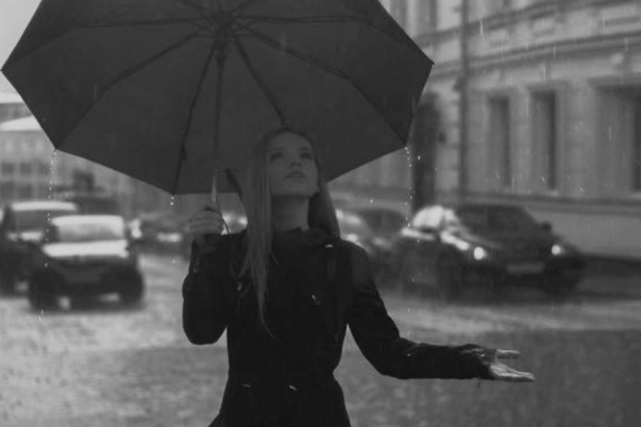 A black and white image of a blonde woman stands in the rain with an umbrella, one hand outstretched. In the background are city streets with parked cars and tall buildings.