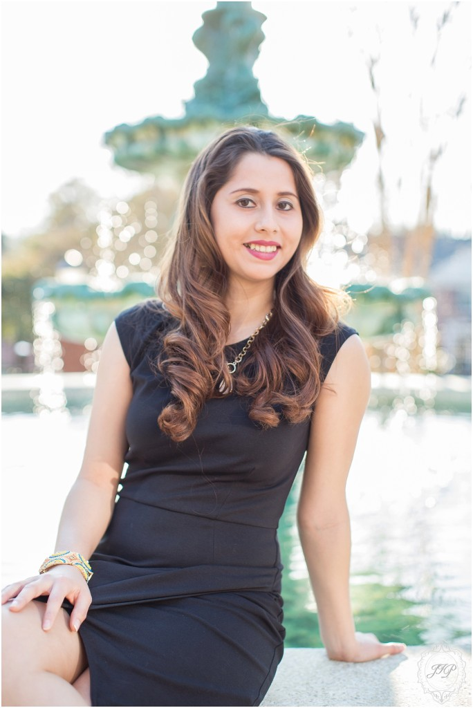 College senior wearing a black dress sitting on the Columbia College fountain and smiling.