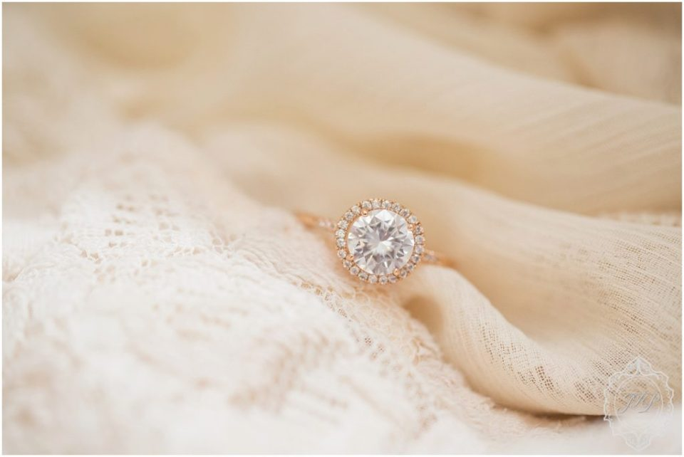 A large rose gold engagement ring sits on a piece of ivory lace in Columbia, South Carolina.