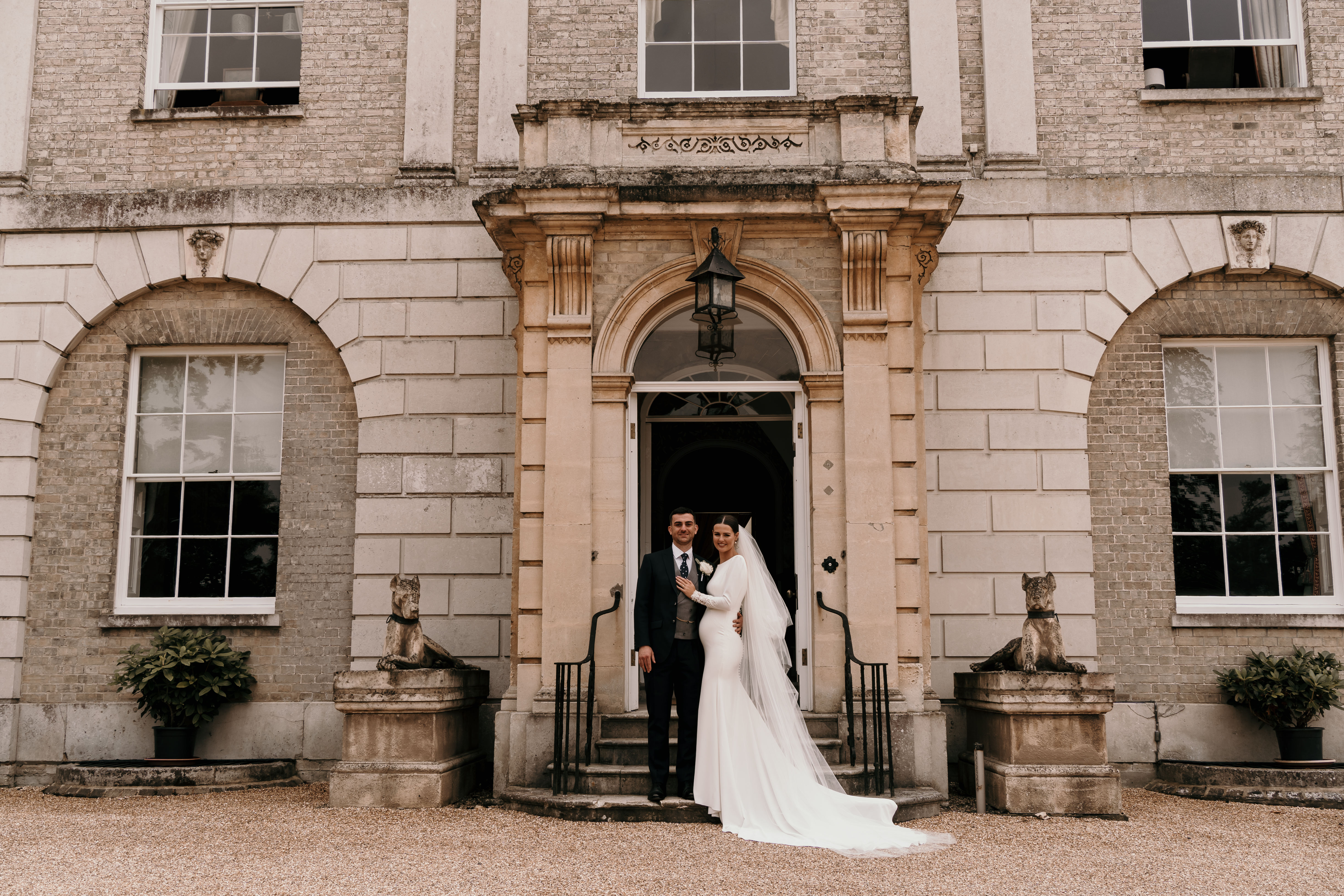 bride and groom posing outside Hatfield place