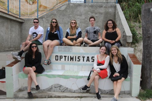 """UM Hillel students visited artist communities while on an Alternative Spring Break trip to Cuba in March 2017. Many of them noted that, despite dilapidation throughout the country, the island's people are resourceful and have a relentless artistic energy. Here, several of the students pose outside of Muraleando with a sign that reads """"optimistas,"""" or optimists. Photo credit: Jessica M. Castillo"""