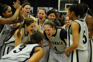 Surrounded by their teammates, Columbia College guards Heather English and Aqua Corpening celebrate after their 91-83 victory over William Woods University in the American Midwest Conference Tournament Championship Monday evening, March 4, 2013, at Southwell Complex.