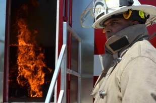 University of Missouri Extension Fire and Rescue Training Institute instructor Dean Martin watches the fire simulation during a training session. This simulator can help teach firefighters to look for the causes of a fire.