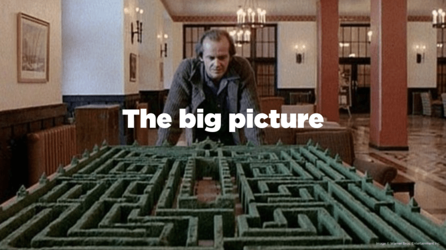Scene from The Shining of Jack Torrance gazing down at a model of the Overlook Hotel's labrynth.